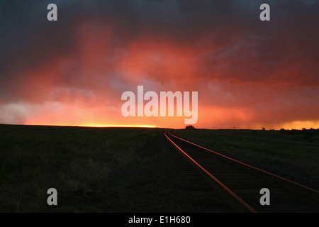Intense sunset colors illuminate the railroad tracks over this remote location, Burlington, Colorado, USA - Stock Photo