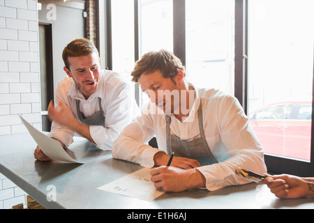 Chefs preparing for service in restaurant - Stock Photo