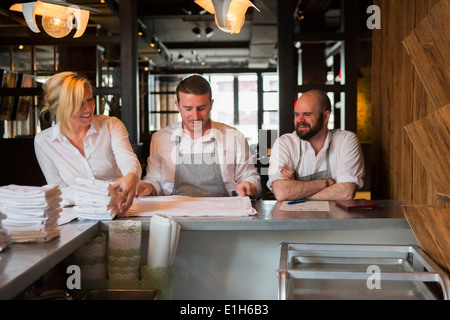 Chefs and waitress preparing for service in restaurant - Stock Photo