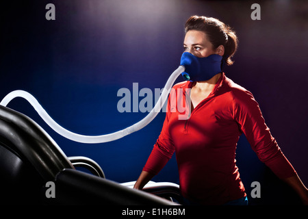 Mid adult woman with face mask on gym treadmill in altitude centre - Stock Photo
