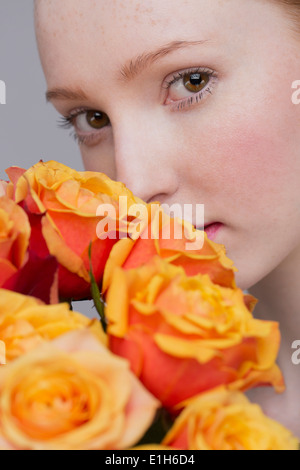 Portrait of young woman, holding bunch of roses - Stock Photo