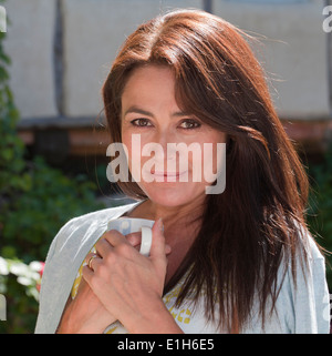 Close up portrait of mature adult woman with coffee mug - Stock Photo