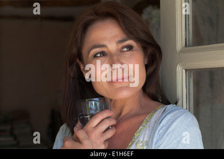 Portrait of mature adult woman with drinking glass - Stock Photo