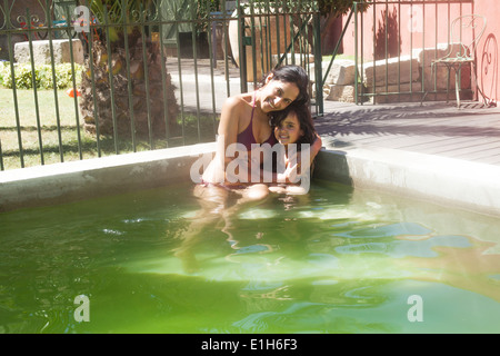Portrait of mother and daughter in outdoor swimming pool - Stock Photo