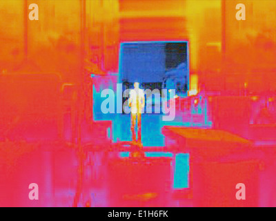 Infra red heat image of worker and heat loss from loading doors in factory - Stock Photo