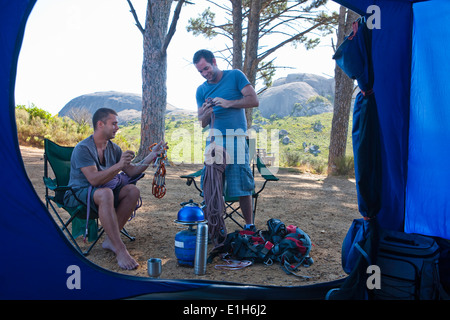 Two young men chatting and preparing camp - Stock Photo