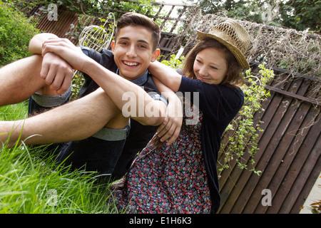 Teenage couple relaxing in garden - Stock Photo