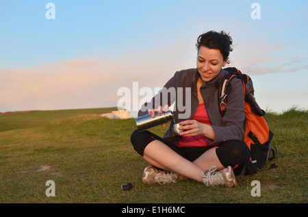 Young female hiker pouring coffee flask on cliff top - Stock Photo