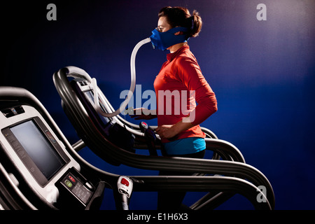 Mid adult woman with face mask running on gym treadmill in altitude centre - Stock Photo