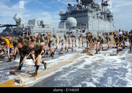 Sailors and Marines with the 11th Marine Expeditionary Unit (11th MEU), scrub down the flight deck of the amphibious - Stock Photo