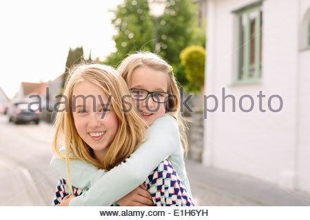 Portrait of two sisters playing piggyback - Stock Photo