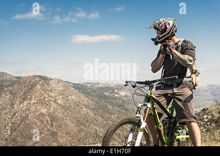 Downhill mountain biker putting on helmet - Stock Photo