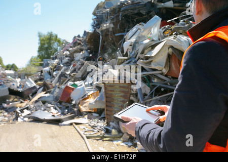 Foreman using digital tablet at scrap metal recycling plant - Stock Photo