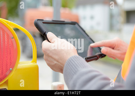 Foremans hands using digital tablet on road construction site - Stock Photo