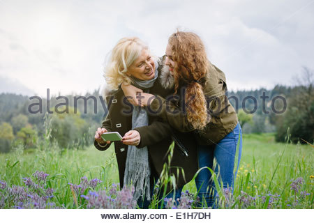 Teenage daughter and mother with smartphone - Stock Photo
