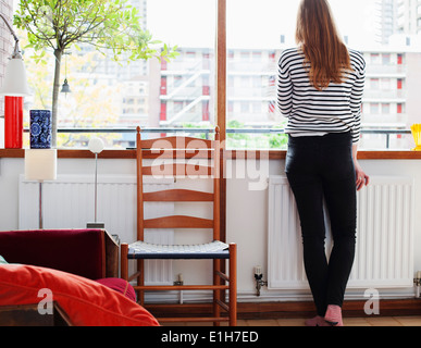 Rear view of young woman looking through window - Stock Photo
