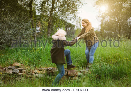 Teenage girl helping her mother over a stone wall - Stock Photo