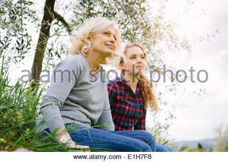 Mother and teenage daughter sitting on grass - Stock Photo