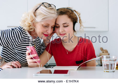 Mother and teenage daughter listening to music on headphones at home - Stock Photo