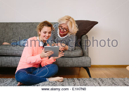 Mother and teenage daughter looking at digital tablet at home - Stock Photo