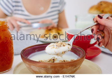 Close up of mother and teenage daughter sharing breakfast - Stock Photo