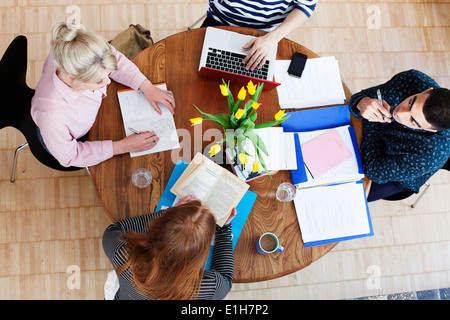 Aerial view of four young adults sitting around table studying - Stock Photo