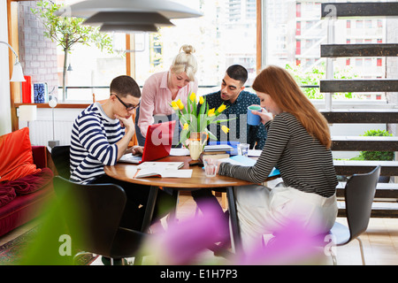 Four young adults sitting around table studying - Stock Photo