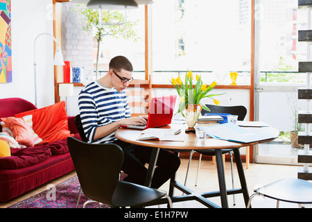 Young man sitting at table using laptop - Stock Photo