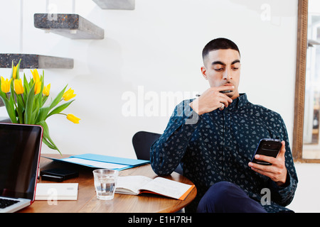 Young man sitting at table, using smartphone - Stock Photo