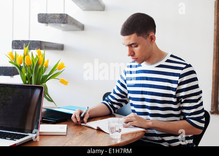 Young man sitting at table, writing in notebook - Stock Photo