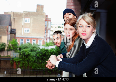 Four young adults, standing on balcony in London, UK - Stock Photo