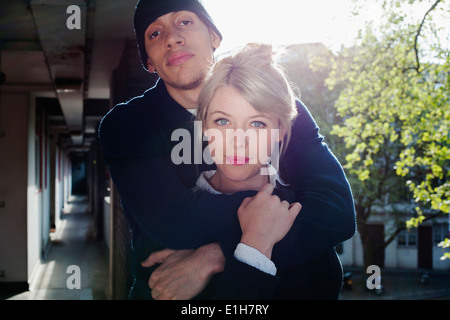Young couple with arm around, standing in block of flats, London, UK - Stock Photo