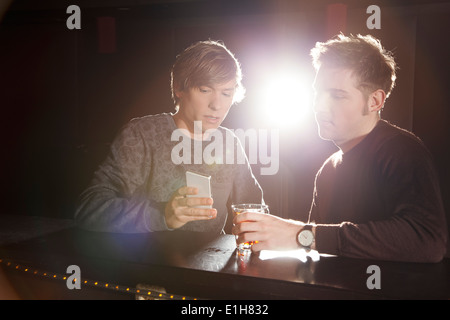Two male friends looking at smartphone in nightclub - Stock Photo