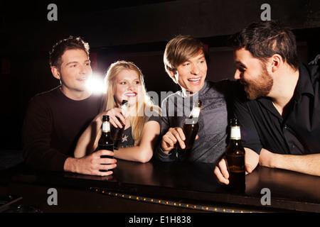 Four friends drinking bottled beer in nightclub - Stock Photo