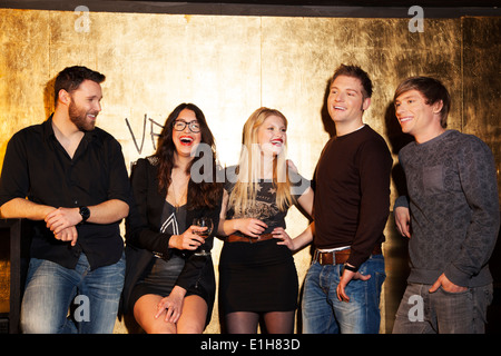 Group of friends having a laugh in nightclub - Stock Photo