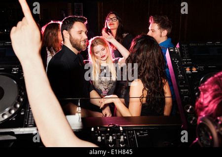 Group of young men and women dancing in front of DJ in nightclub - Stock Photo