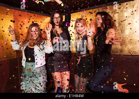 Four female friends partying in nightclub - Stock Photo