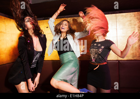 Four female friends dancing in nightclub - Stock Photo