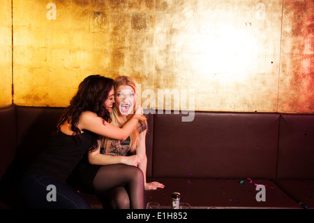 Two female friends having a laugh in nightclub - Stock Photo