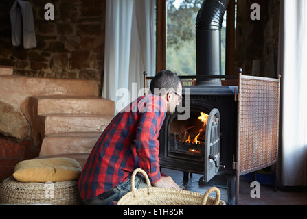 Mid adult man watching log burning fire - Stock Photo