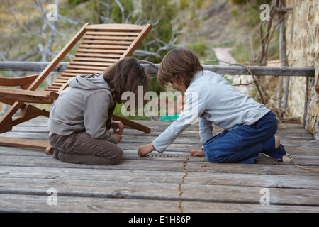 Brother and sister making a row of dried beans on balcony - Stock Photo