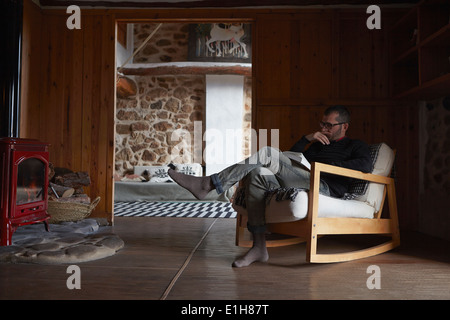 Mid adult man reading book in sitting room - Stock Photo