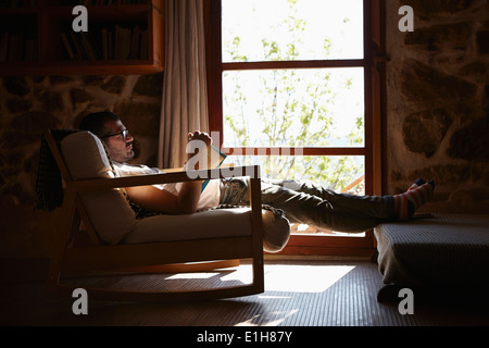 Mid adult man reading book whilst relaxing in sitting room - Stock Photo