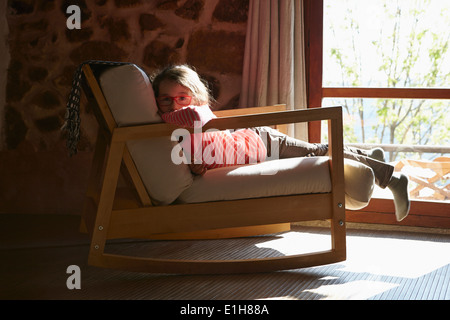 Portrait of young girl lying on rocking chair - Stock Photo