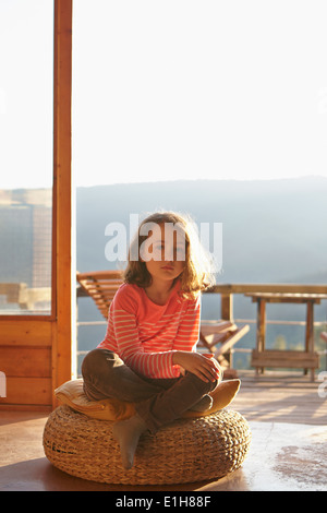 Portrait of young girl sitting on hassock - Stock Photo