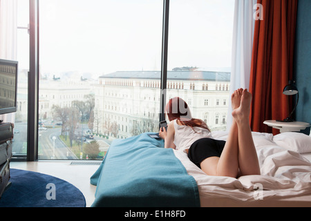 Young woman in hotel room overlooking street - Stock Photo