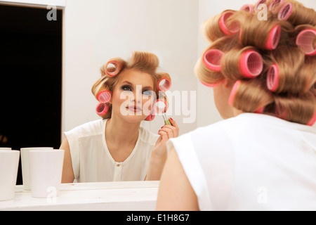 Young woman in curlers putting on make-up - Stock Photo