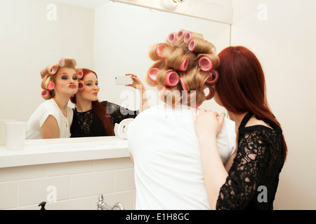 Young woman in curlers and friend taking selfie - Stock Photo