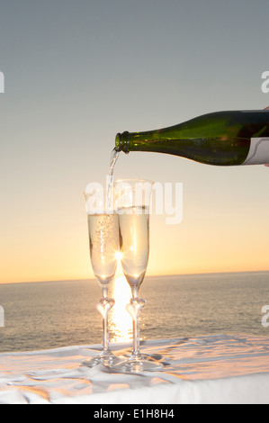 Champagne being poured into flute against sunset - Stock Photo