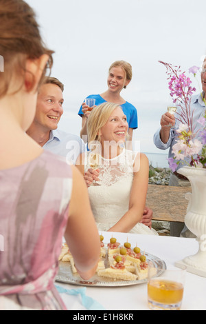 Mid adult couple making a toast with group of friends at wedding reception - Stock Photo